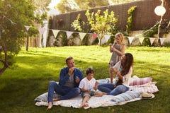 Parents soufflant des bulles avec des enfants sur la couverture dans le jardin photographie stock