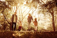 Smiling family in park together. Parents spending day in park with daughters royalty free stock image