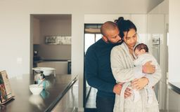 Parents spending time with newborn son in morning. Young father and mother holding their baby boy in kitchen. Parents spending time with newborn son at home in stock images