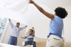 Parents Spreading Bedsheet Over Son Stock Image