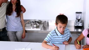 Parents standing next to children doing their homework stock video footage