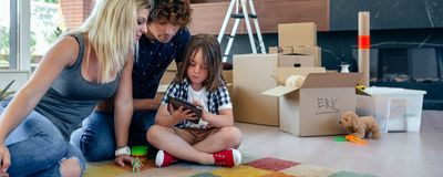 Parents supervising their little son playing tablet. Parents supervising their little son playing the tablet sitting on the floor of the living room stock photography