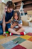 Parents supervising their little son playing tablet. Parents supervising their little son playing the tablet sitting on the floor of the living room royalty free stock images