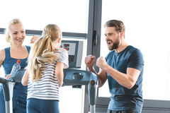 Parents supporting daughter workout on treadmill Royalty Free Stock Image