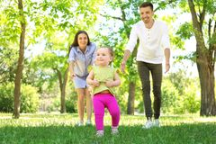 Parents supporting their baby daughter while she learning. To walk outdoors stock photos
