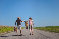 Parents swinging babe girl on countryside highway Royalty Free Stock Images