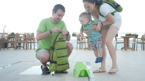 Parents take a baby pot from the backpack and put a son on it. Family in a restaurant near the sea stock video