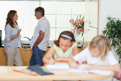 Parents talking with children doing homework in front of them Stock Images