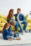 Parents talking while kids. Using laptop royalty free stock images