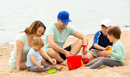 Parents talking and kids playing with sand Stock Photos