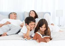 Parents talking while their childrens are reading. On the bed Royalty Free Stock Photos