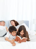 Parents talking while their childrens are reading. On the bed Royalty Free Stock Image