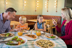 Parents talking to children in restaurant. Parents talking to children at table in restaurant royalty free stock image
