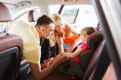 Parents talking to little girl in baby car seat. Family, transport, safety, road trip and people concept - happy parents talking to little girl in baby car seat royalty free stock images