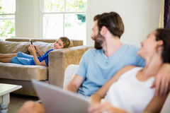 Parents talking to a son while using laptop. At home stock photo