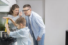 Parents tasting food while son preparing food in kitchen royalty free stock photos