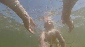 Parents teach a small one-year-old child to dive underwater in the sea. Parents teach a small one-year-old child to dive underwater in the sea stock video footage