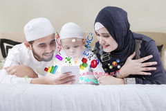 Parents teach their child on the bed Stock Photography