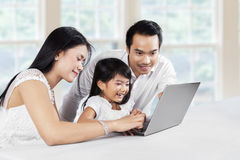 Parents teach their daughter to use laptop Royalty Free Stock Photo