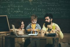 Parents teaches son, chalkboard on background. Boy listening to mom and dad with attention. Family cares about education. Of their son. Homeschooling concept Royalty Free Stock Images