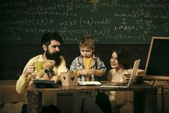 Parents teaches son, chalkboard on background. Boy listening to mom and dad with attention. Family cares about education royalty free stock photos