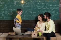 Parents teaching kid at home. Boy presenting his knowledge to mom and dad. Parents listening their son, chalkboard on. Background. Homeschooling concept. Smart royalty free stock photography