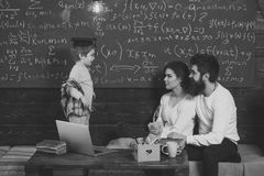 Parents teaching kid at home. Boy presenting his knowledge to mom and dad. Parents listening their son, chalkboard on. Background. Homeschooling concept. Smart royalty free stock photo