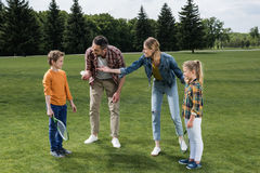 Parents teaching little kids how to play badminton. Outdoors Stock Photo