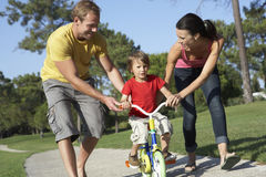 Parents Teaching Son To Ride Bike In Park Stock Photos