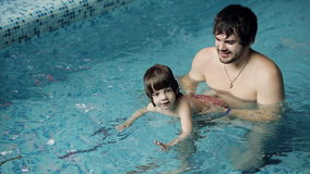 Parents teaching their son to swim in the pool. stock footage