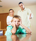 Parents and teen son having quarrel. At home. Focus on boy Royalty Free Stock Photography