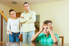 Parents and teenager having conflict at home. Focus on boy royalty free stock images