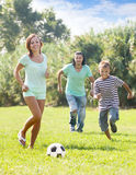 Parents with teenager son playing with soccer ball stock photo