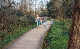 Parents tenant la fille à la main pour sauter dans la forêt Photo stock
