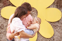 Parents with their baby girl in the park. Playful parents with their baby girl in the park Royalty Free Stock Photography