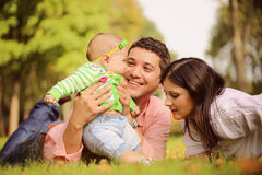 Parents with their baby girl sitting on the grass Stock Photography