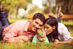 Parents with their baby girl sitting on the grass Royalty Free Stock Photos