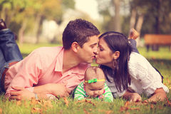 Parents with their baby girl sitting on the grass Royalty Free Stock Image