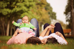 Parents with their baby girl sitting on the grass Royalty Free Stock Photography