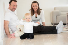 Parents and their beautiful baby girl sitting on the ground and playing. Stock Photos