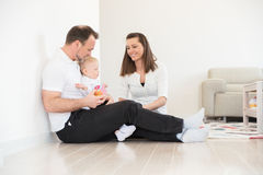 Parents and their beautiful baby girl sitting on the ground and playing. Royalty Free Stock Photo