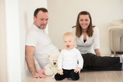Parents and their beautiful baby girl sitting on the ground and playing. Stock Photography