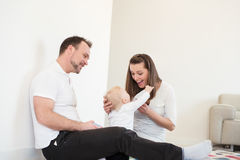 Parents and their beautiful baby girl sitting on the ground and playing. Royalty Free Stock Photography
