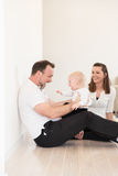 Parents and their beautiful baby girl sitting on the ground and playing. Happy family of three  is enjoying at home. Parents and their beautiful baby girl Royalty Free Stock Photo