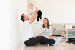 Parents and their beautiful baby girl sitting on the ground and playing. Royalty Free Stock Photos