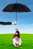 Parents and their child lying on grass under umbrella. Portrait of two young parents lying on the grass with their little daughter under umbrella. Life and Royalty Free Stock Image