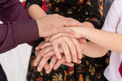 Parents and their children hold hands together. The hands of children and parents piled on each other stock photo