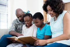 Parents and their children looking at photo album in living room Stock Photography