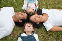 Parents and their children lying on the grass. Jolly parents and their children lying on the grass in a park Stock Photo