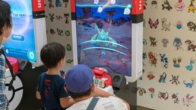 Parents with their children playing Pokemon branded arcade video games at Pokemon Center, Tokyo, Japan. Tokyo, Japan - August 2018: Parents with their children stock images